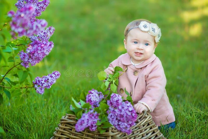 Guirlande de port an de sourire de fleur du bébé 1-2, tenant le bouquet du lilas dehors regarder l'appareil-photo printemps d'été photos libres de droits