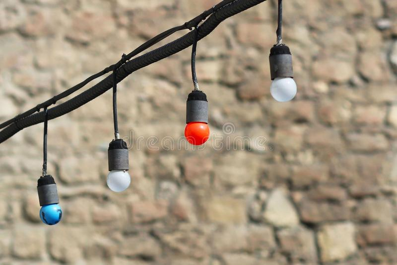 Guirlande des ampoules colorées avec une ampoule rouge au centre Éclairage de fête de rue sur le fond d'une pierre brouillée images libres de droits