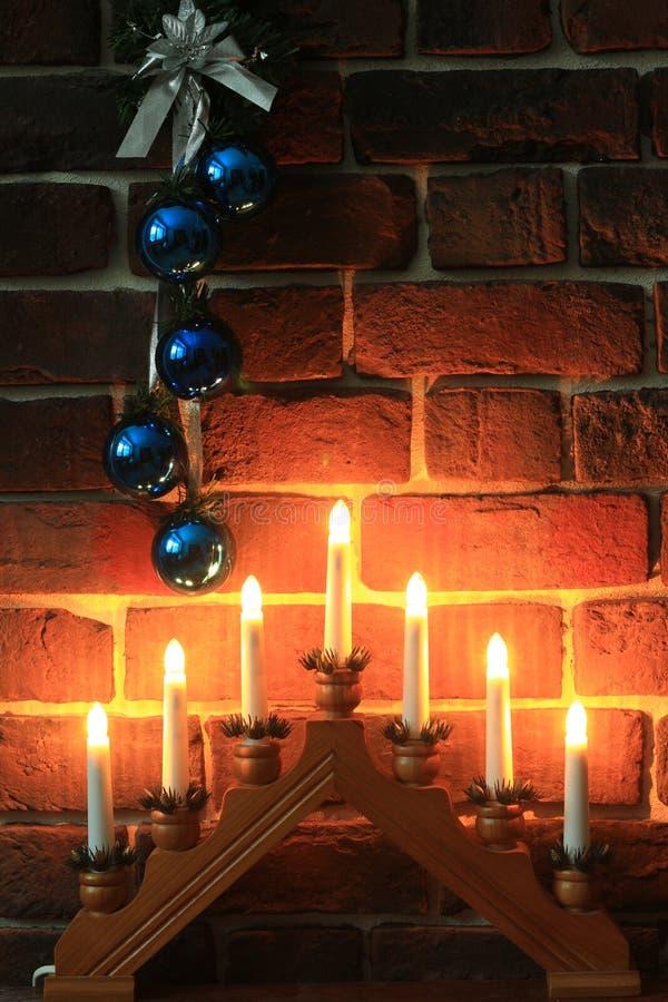 Guirlande des boules bleues et un chandelier près d'un mur de briques photos stock