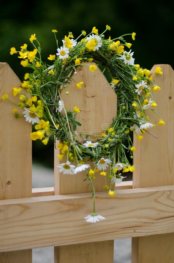 Guirlande des fleurs sauvages sur la barrière en bois photographie stock libre de droits