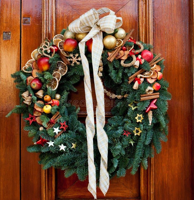Guirlande extérieure fabuleuse de Noël ornementée avec le fruit artificiel contre la porte en bois photo stock