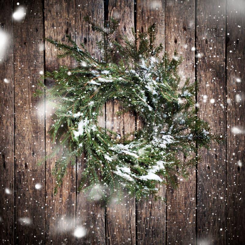 Guirlande naturelle verte sur le fond en bois avec la neige en baisse photos stock