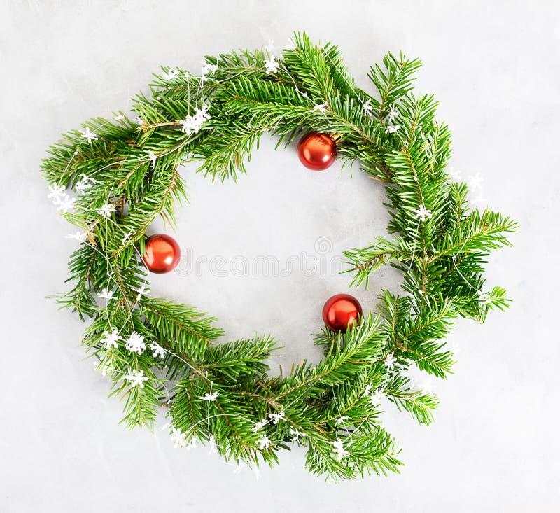 Guirlande verte de Noël de configuration d'appartement de vue supérieure avec les boules et les snwflakes rouges de papier sur le photographie stock