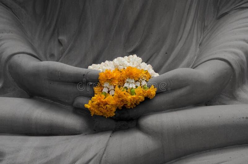 Guirnalda amarilla en las manos de la estatua de Buda blancos y negros imagenes de archivo