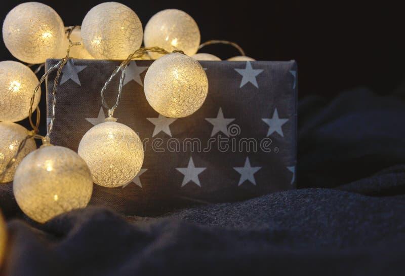 Guirnalda blanca de la luz de la bola de algodón en una cesta gris con las estrellas que chispean en casa cerca para arriba, luce foto de archivo
