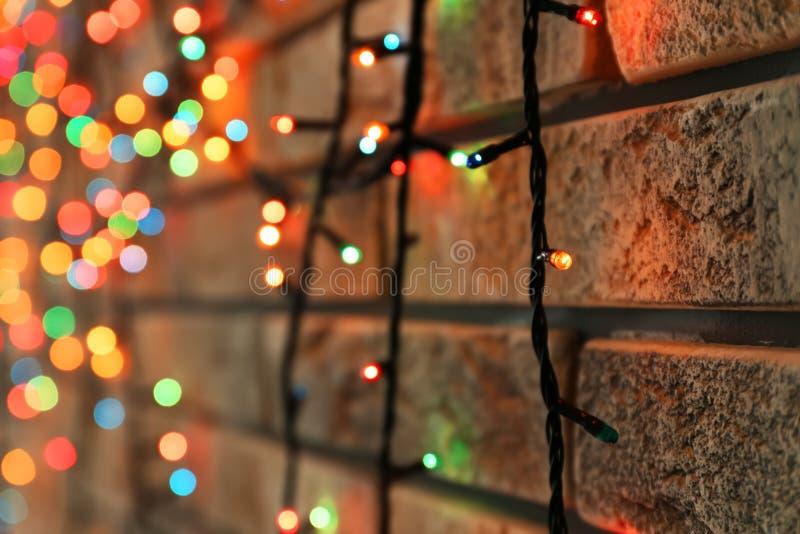 Guirnalda brillante hermosa de la Navidad cerca de la pared de ladrillo, primer fotografía de archivo libre de regalías