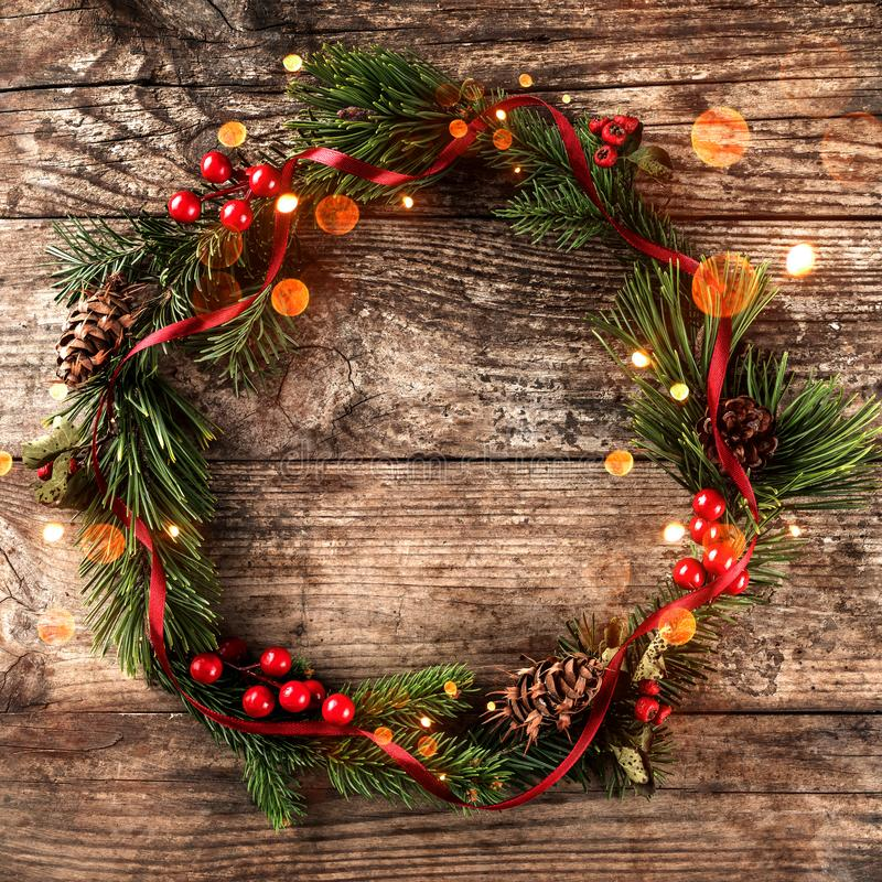 Guirnalda de la Navidad de las ramas del abeto, de los conos del pino, de las bayas y de la cinta roja en fondo de madera imagen de archivo libre de regalías