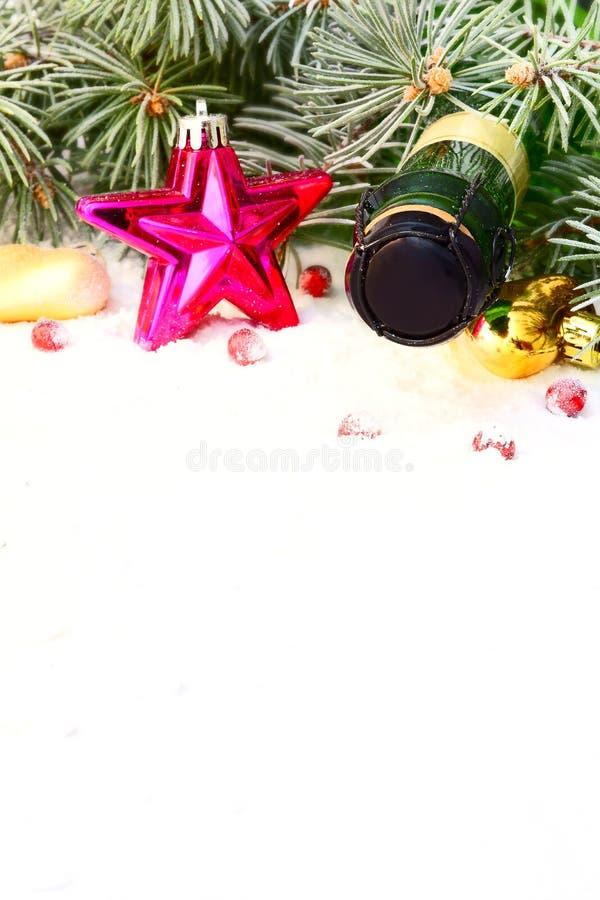 Guirnalda de la Navidad y una botella de champán imagen de archivo