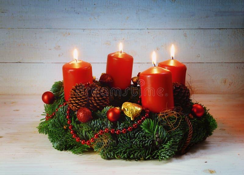Guirnalda del advenimiento con cuatro velas y decoros ardientes rojos de la Navidad fotografía de archivo