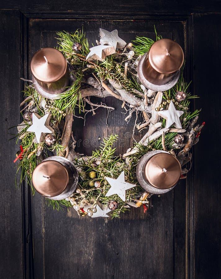 Guirnalda del advenimiento con deco de la Navidad y cuatro velas fotos de archivo