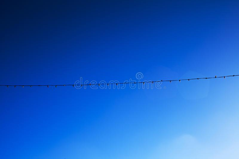 Guirnalda eléctrica larga del cielo azul para encenderse con las bombillas blancas contra la perspectiva de un cielo claro azul imagen de archivo libre de regalías