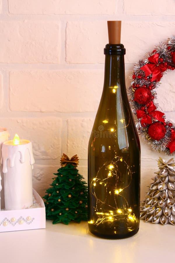 Guirnalda en la botella Botella vacía del champán con la guirnalda dentro en la tabla blanca Decoración que brilla intensamente p imagen de archivo