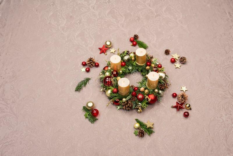 Guirnalda hecha a mano fresca de la Navidad adornada con rojo y decoraciones de la Navidad del oro, abeto-conos y nueces con las  foto de archivo libre de regalías