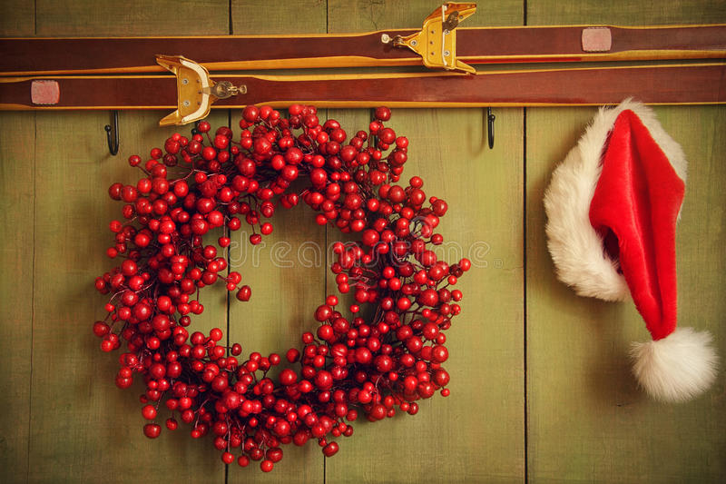Guirnalda roja con el sombrero de Santa que cuelga en la pared rústica fotografía de archivo
