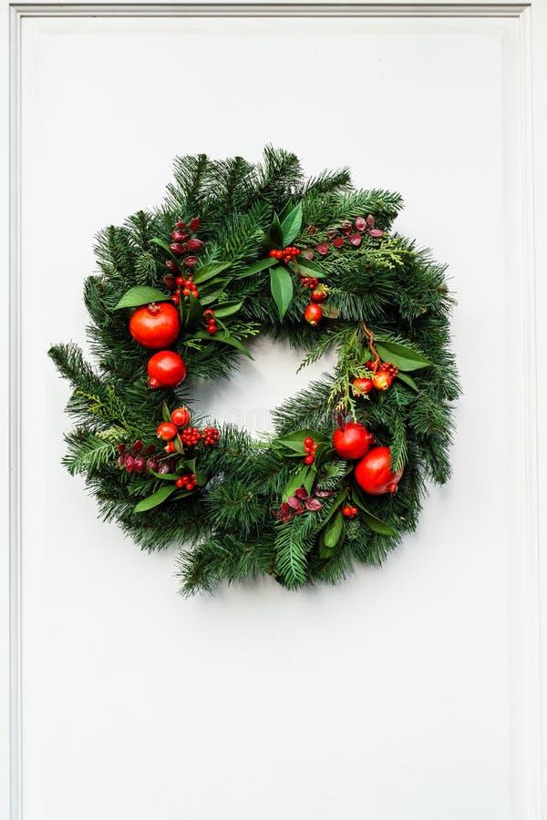 Guirnalda verde de la Navidad con la granada y las bayas rojas en la puerta blanca foto de archivo