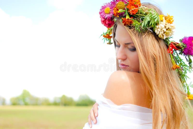 Guirnalda y blanco de la flor de la muchacha que lleva encantadora foto de archivo