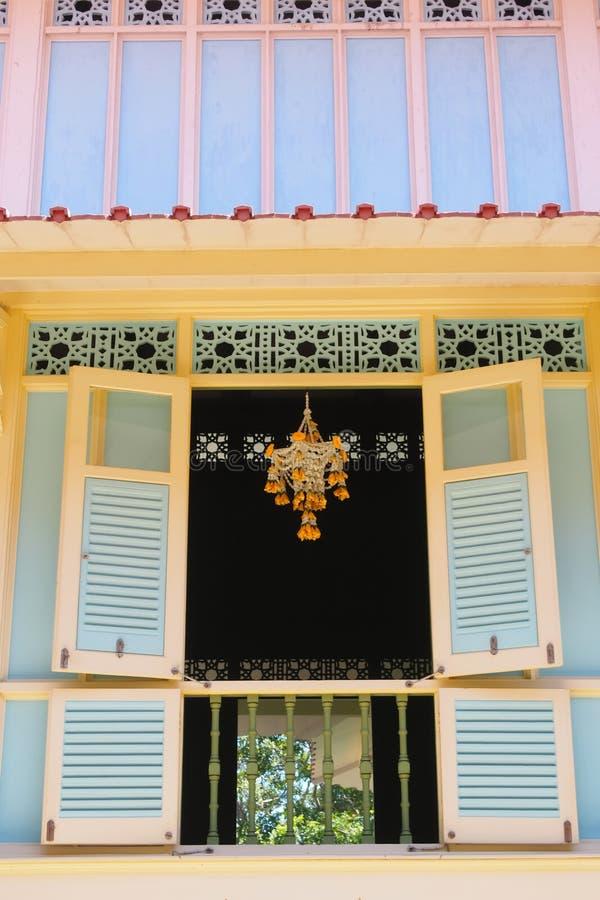 Guirnaldas de las flores que cuelgan en las ventanas de edificios amarillos y azules en ?reas p?blicas foto de archivo