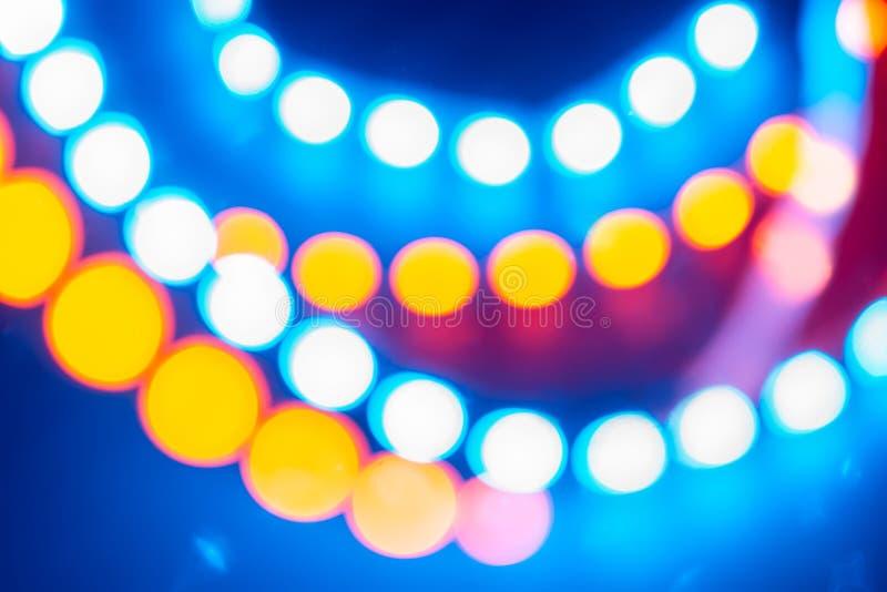 Guirnaldas de neón amarillas azules rojas de las luces del bokeh Fondo festivo de colores retros imagenes de archivo