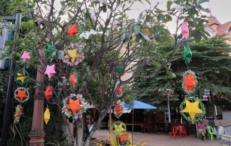 Guirnaldas festivas y decoraciones que cuelgan de árboles Muchas estrellas coloridas en chispas adornan imágenes de archivo libres de regalías