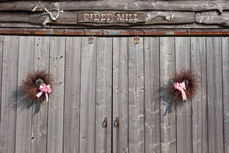 Guirnaldas hechas a mano del verano que cuelgan en puertas de granero viejas imágenes de archivo libres de regalías