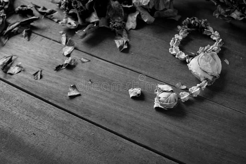 Guirnaldas secadas de la flor con las hojas secadas en piso de madera fotos de archivo