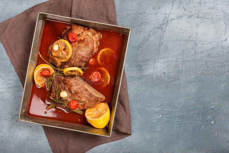 Guisado cocido de la carne de la carne de vaca con los tomates, el limón, el ajo y el romero imagen de archivo
