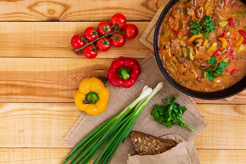 Guisado con la carne y las verduras en salsa de tomate en fondo de madera Visi?n superior imagenes de archivo