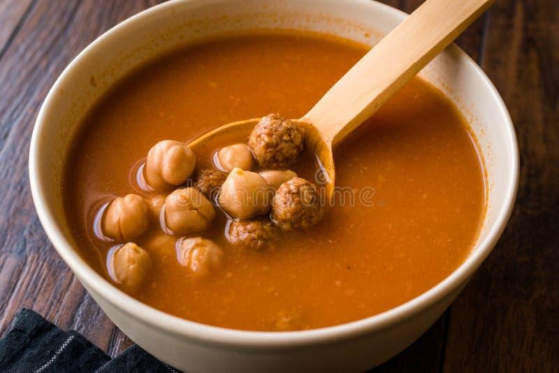 Guisado da sopa do grão-de-bico com almôndegas e a colher/Espanhol de madeira Potaje de Grão-de-bico foto de stock