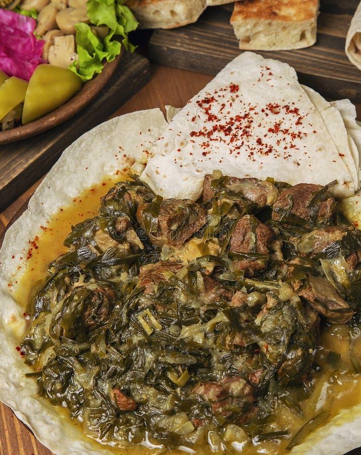 Guisado de la carne, turshu, govurma del sebze con las cebollas, hierbas verdes, zanahorias en salsa del caldo fotos de archivo