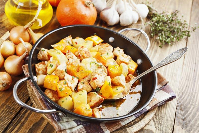 Guisado de pollo con la calabaza, las patatas y las especias foto de archivo