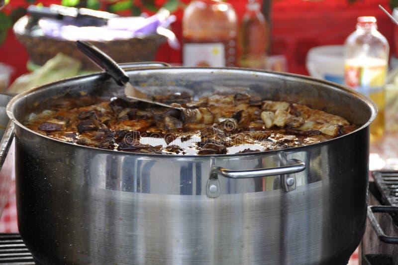 Guisado no potenciômetro do metal na toalha de mesa da manta Alimento tradicional de Balcãs imagem de stock royalty free