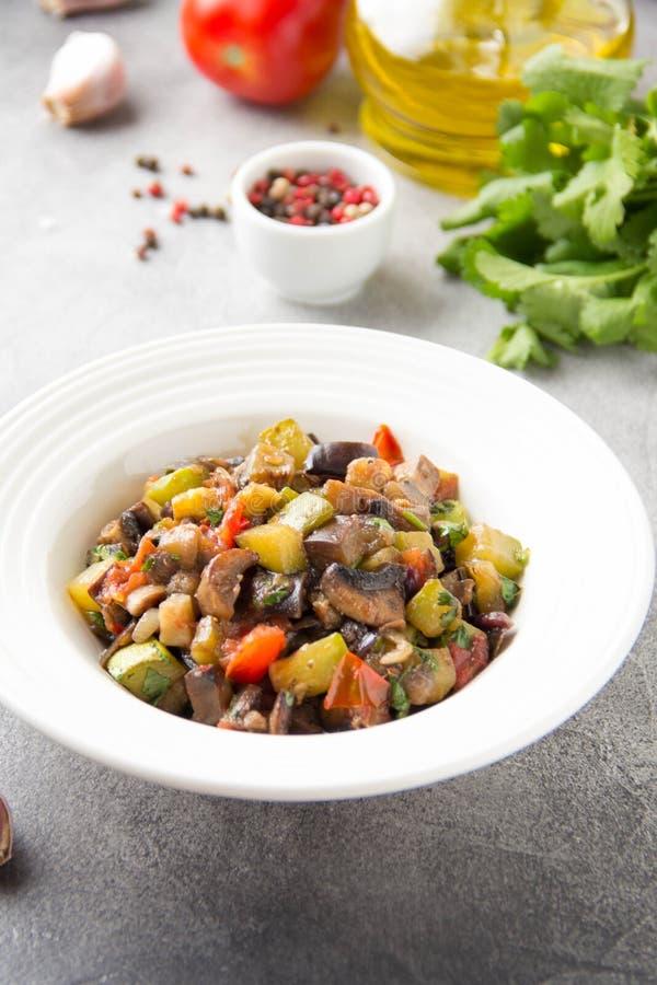 Guisado vegetal con la berenjena, el calabacín, los tomates, las cebollas, las setas, el ajo y el cilantro Ajapsandali vegetarian imagen de archivo
