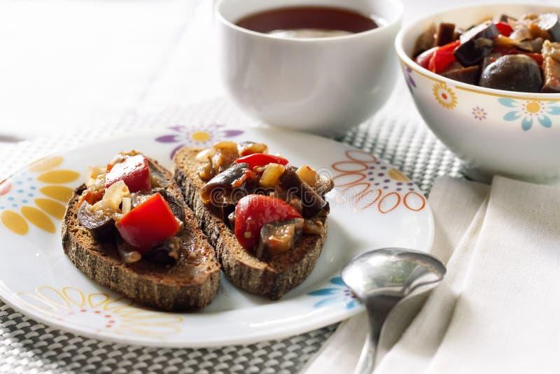 Guisado vegetal con la berenjena, la pimienta roja y los tomates en el pan tostado foto de archivo libre de regalías