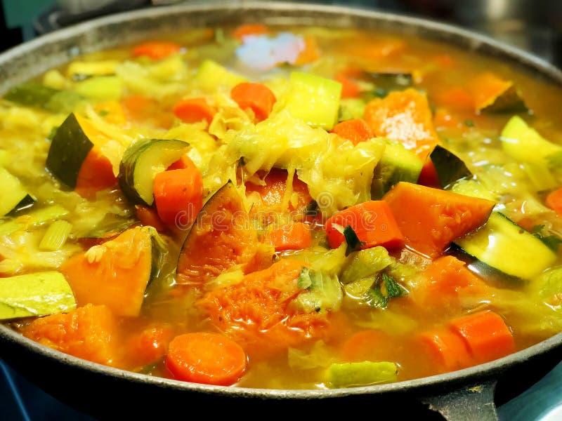 Guisado vegetal con los prendederos en una placa Zanahorias guisadas, habas verdes, habas rojas, guisantes, maíz, pimientas y ceb imagenes de archivo