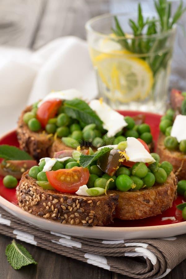 Guisantes verdes con los tomates, el queso feta y la menta de cereza en tostada imagen de archivo