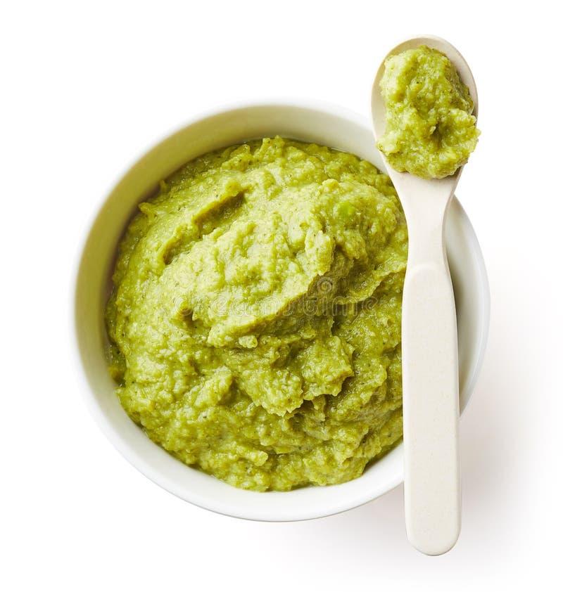 Guisantes verdes y puré del bebé del bróculi en blanco fotos de archivo