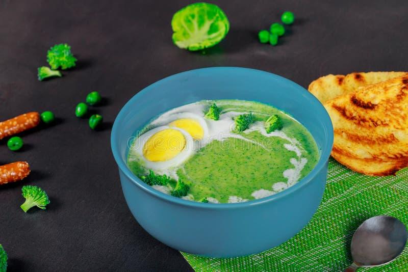 Guisantes verdes y sopa hechos en casa del bróculi, fondo de madera oscuro imagen de archivo