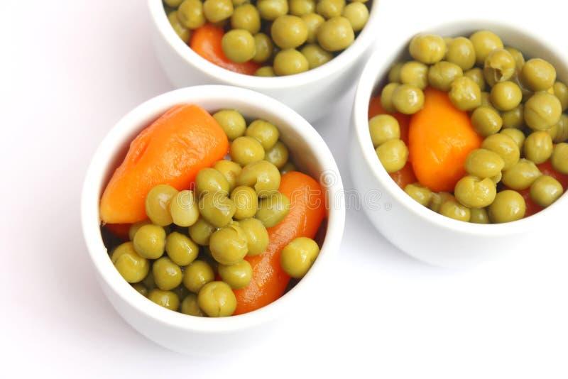 Guisantes y zanahorias en cuencos imagenes de archivo
