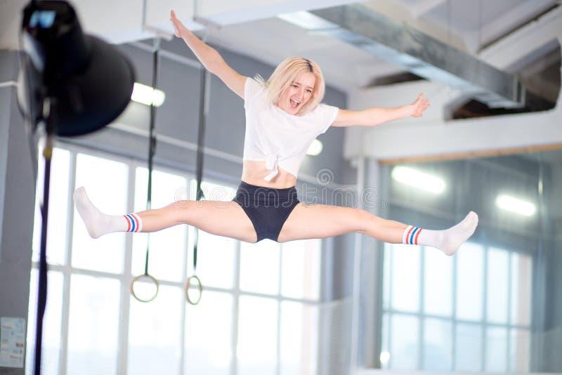 Guita que salta a la mujer joven en el trampolín fotos de archivo