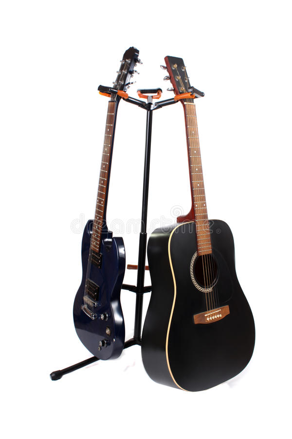 Guitar. Accoustic and electric guitars on a stand with a white background royalty free stock image