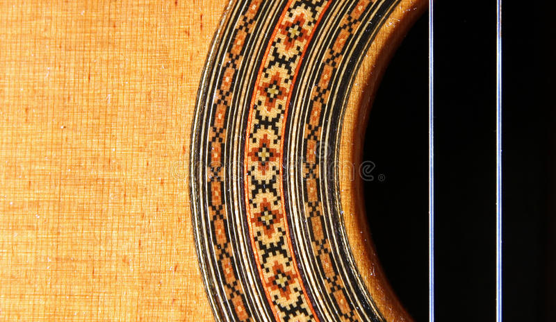 Guitar Abstract. Classial (spanish) guitar abstract showing sound hole with ornate decoration and two nylon strings with left part of image blank for copy royalty free stock photos