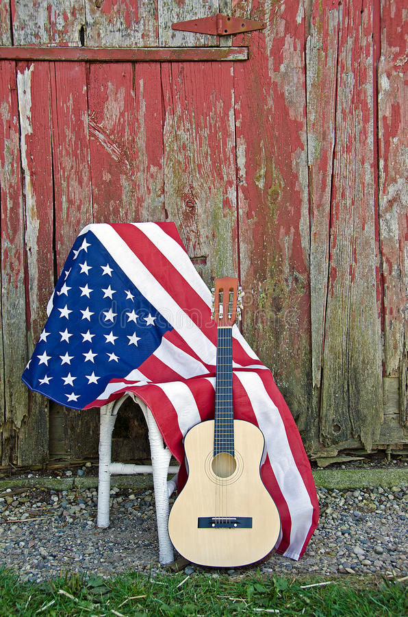 Guitar with American flag. By old red barn royalty free stock images