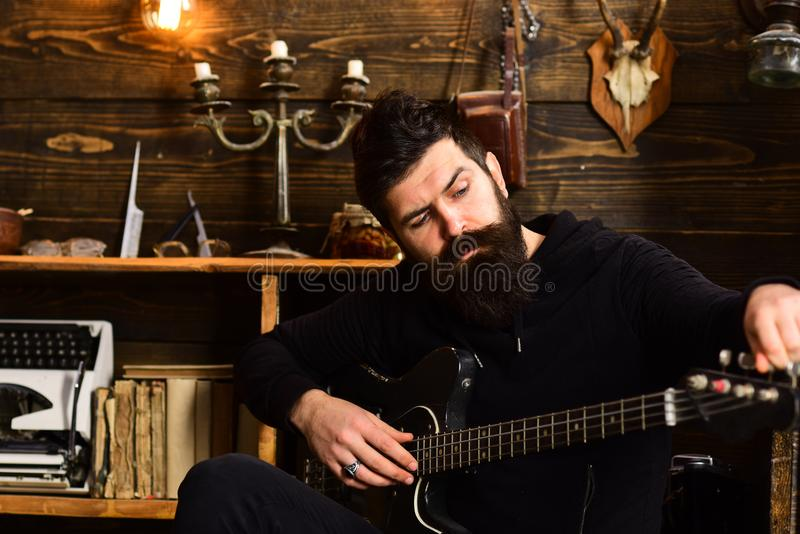 Guitar as hobby. Guy in cozy warm atmosphere play favourite music. Man with beard holds black electric guitar. Man royalty free stock photo