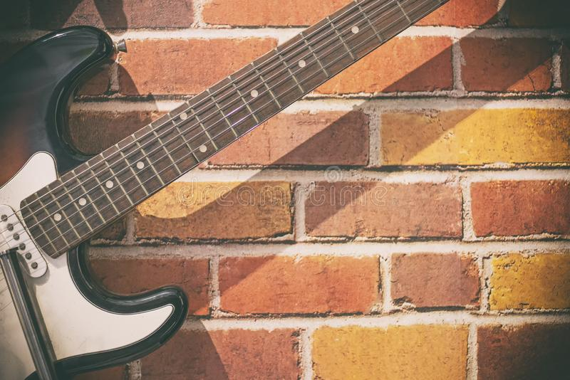 Guitar on a brick wall for life style royalty free stock image