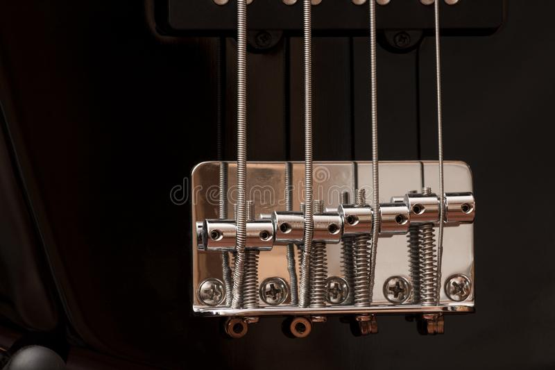 The guitar bridge. The strings of a bass guitar close up. Musical instrument. Black glossy paint. Musical art.  royalty free stock image
