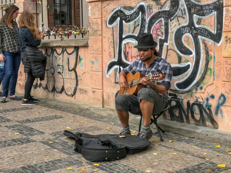 Guitar busker in front of graffitied wall, Prague, Czechoslovakia. Oct 2017: Guitar busker ists in front of graffiti wall near tourists in Prague, Czechoslovakia royalty free stock image
