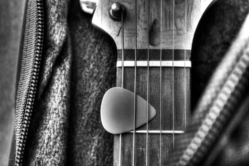 Guitar in the case. Guitar and pick in the case in HDR Black and White stock photo