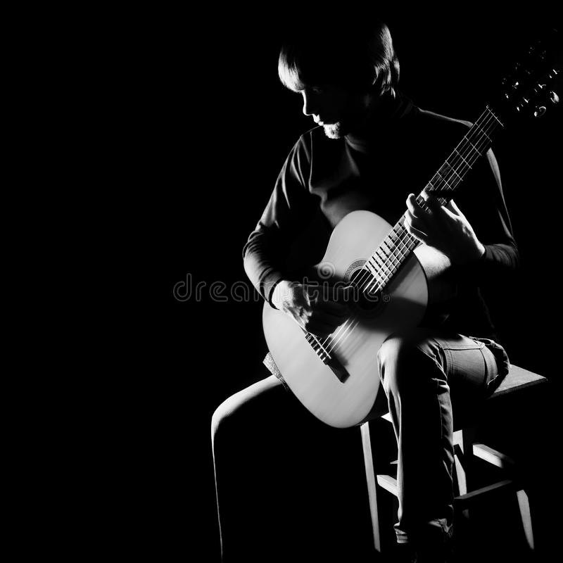 Guitar concert guitarist in darkness. Guitar concert player Acoustic guitarist in darkness playing classical music instruments stock images