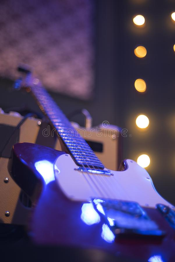 Guitar at a concert. On stage in the rays of light royalty free stock photography