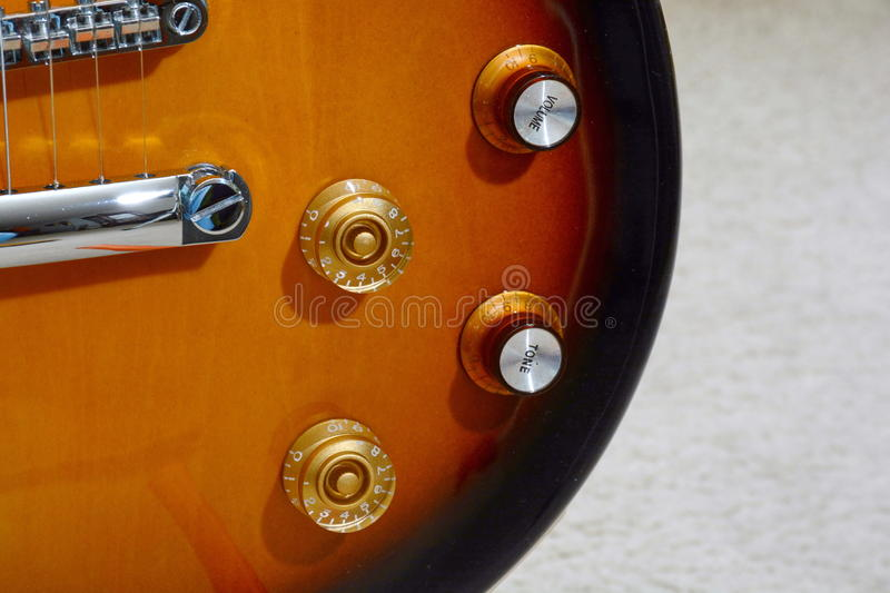Guitar Detail. Electric guitar detail section with tone and volume controls, bridge and saddle royalty free stock photo